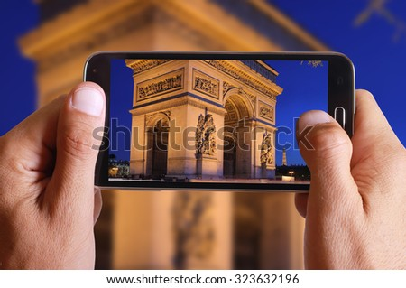 Male hand taking photo of triunfal arc in Paris with cell, mobile phone. French holiday. - stock photo