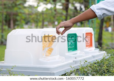 Male hand throwing empty plastic bottle into the trash. - stock photo