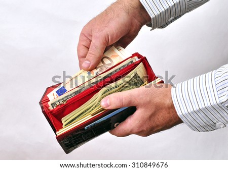Male hand to get money from a red purse full of currency notes