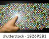 male hand touching with the finger a wall of multiple colorful micro screens - stock photo