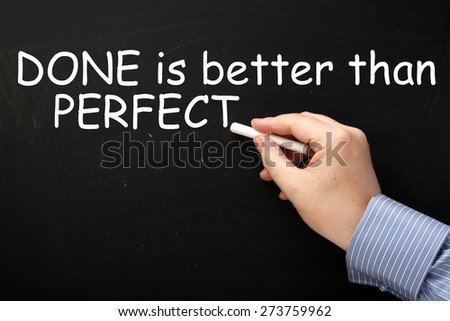 Male hand wearing a business shirt writing the phrase Done Is Better Than Perfect on a blackboard in white text.