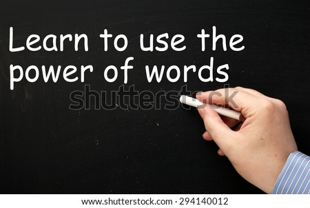 Male hand wearing a business shirt writing the phrase Learn to use the Power of Words in white text on a blackboard - stock photo