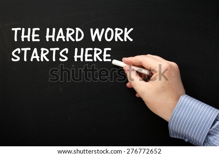 Male hand wearing a business shirt writing the phrase The Hard Work Starts Here on a blackboard in white text