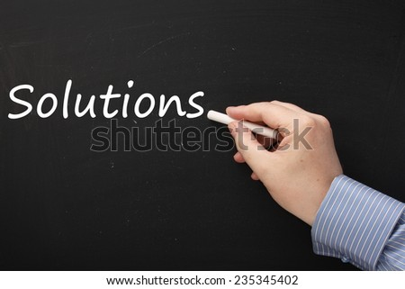 Male hand wearing a business shirt writing the word Solutions on a blackboard using a stick of white chalk - stock photo
