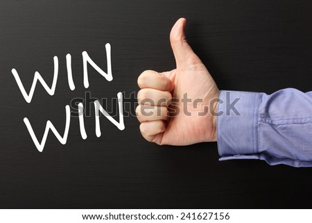 Male hand wearing  business shirt giving a thumbs up gesture to the phrase Win Win written on a blackboard - stock photo