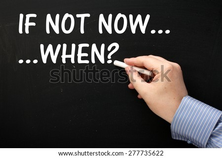 Male hand wearing  business shirt writing the Question If Not Now When? on a blackboard in white text - stock photo