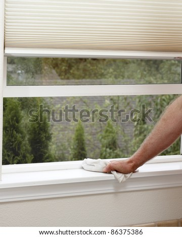 Male hand wiping off a window sill to reduce allergens in the home. - stock photo