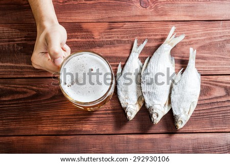 Male hand with a glass of beer and dried fish, traditional russian snack. Wooden background. - stock photo
