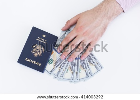 Male hand with american passport and dollars on white surface - stock photo