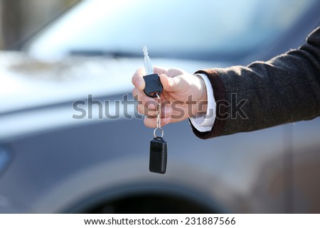 Male hand with car key on car background - stock photo