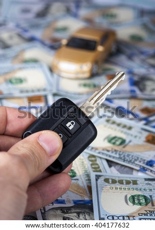 Male hand with car key on the background of  toy car on dollar bills. Selective focus - stock photo