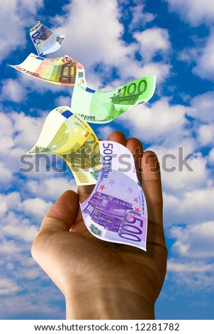 male hand with euro banknotes flying out in the sky - stock photo