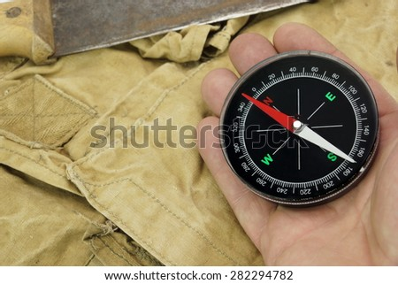 Male Hand With Magnetic Compass And Machete On The Faded Green Backpack Background Close-up - stock photo