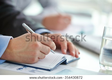 Male hand with pen before writing business ideas in notebook