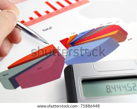 Male hand with pen on pie investment chart with calculator - stock photo