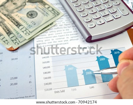 Male hand with pen on the investment chart with calculator and dollars - stock photo