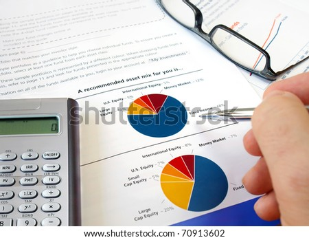 Male hand with pen on the pie investment chart with calculator and glasses - stock photo