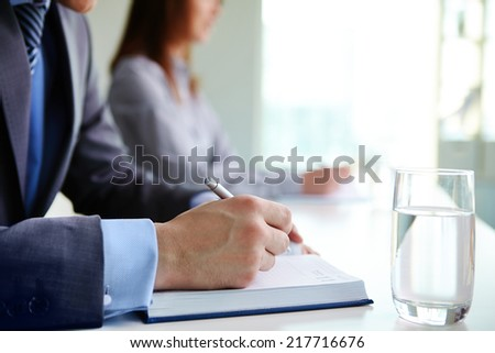 Male hand with pen over open notebook at seminar or conference - stock photo