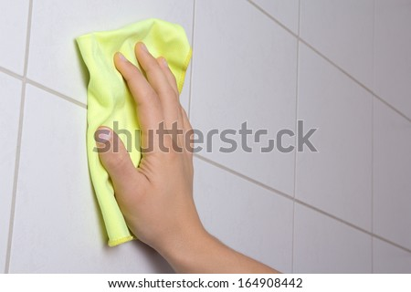 male hand with rag cleaning the bathroom tiles - stock photo