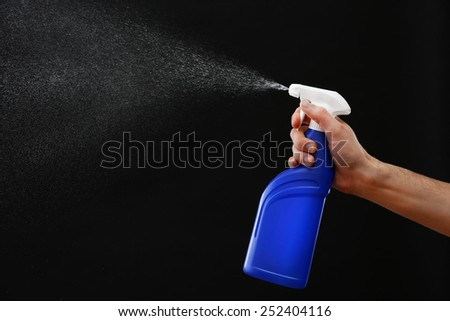 Male hand with sprayer on black background - stock photo