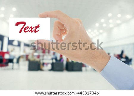Male hand with white blank card on blurred cafe interior - stock photo