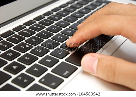 male hand writing on laptop design keyboard with black keys - stock photo