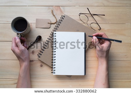 Male hand writing on opened notebook with a cup of coffee on wooden table. Top view. Writing concept - stock photo