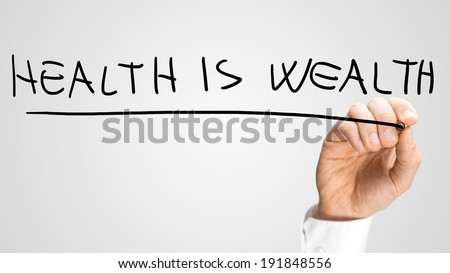Male hand writing phrase Health is Wealth on virtual screen. - stock photo