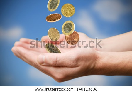 Male hands and falling Euro coins - stock photo