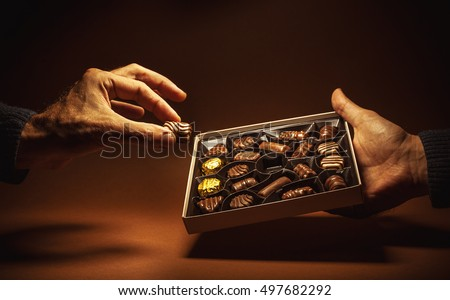 Male hands are holding an open box of chocolates and pick one.