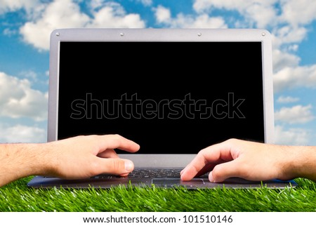 male hands are working on laptop on grass outdoors - stock photo