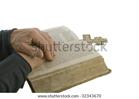 Male hands closed in prayer on an open bible isolated over white - stock photo