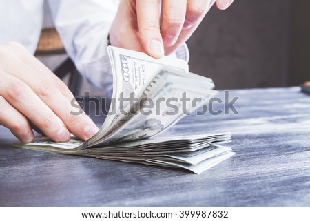 Male hands counting dollars on dark wooden surface