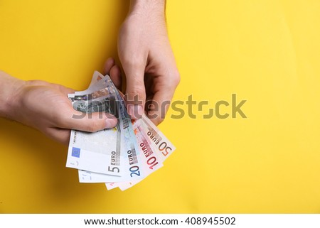Male hands counting euro banknotes on yellow background