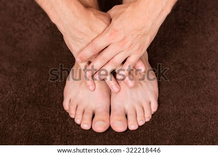 Male hands crossed over healthy resting feet. - stock photo