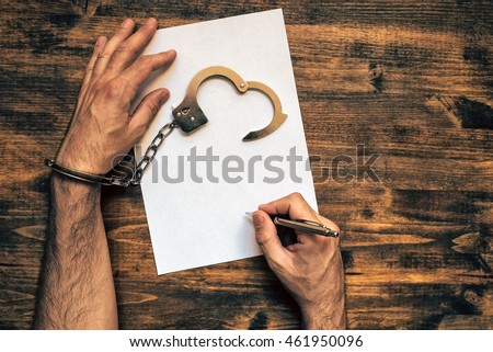 Male hands cuffed signing confession, top view of police investigator detective desk