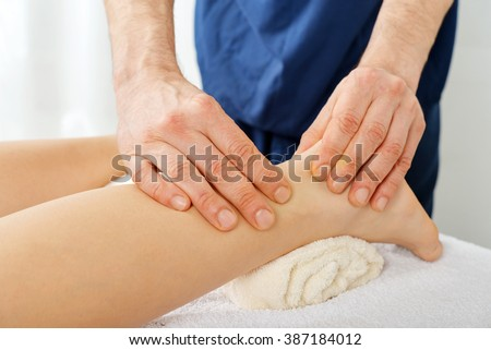 Male hands doing legs massage close-up