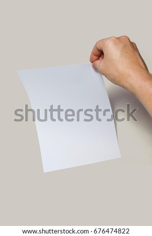 Male hands holding a blank paper on a gray background.