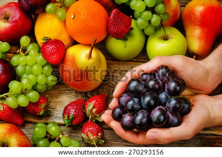 male hands holding a grape on the fruit background. the toning. selective focus - stock photo