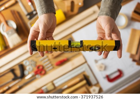 Male hands holding a level, work table with construction and repair tools top view, do it yourself and home renovation concept - stock photo