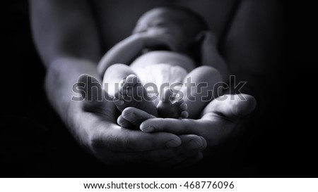 male hands holding a newborn baby, monochrome image, low key effect