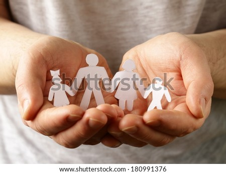 male hands holding a paper human family - stock photo