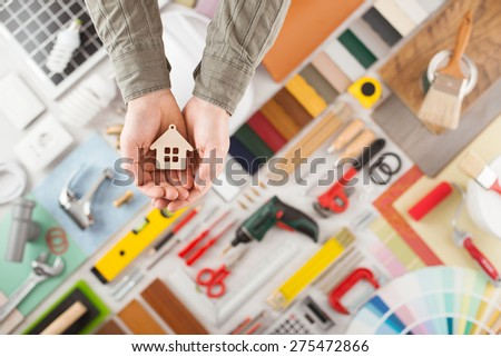 Male hands holding a small house, build and renovation tools on background top view, home insurance concept - stock photo