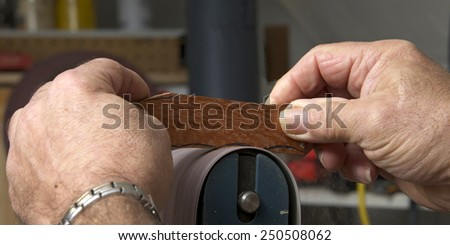 Male hands holding a small piece of cut wood to a table mounted belt sander to smooth the edges on a wood working project. Saw dust everywhere. - stock photo
