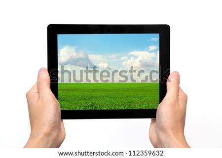 male hands holding a tablet touch computer gadget with the image of green grass and blue sky