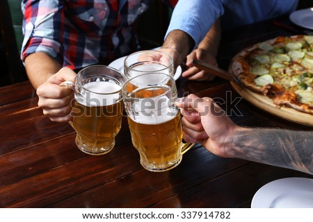 Male hands holding glasses with beer - stock photo