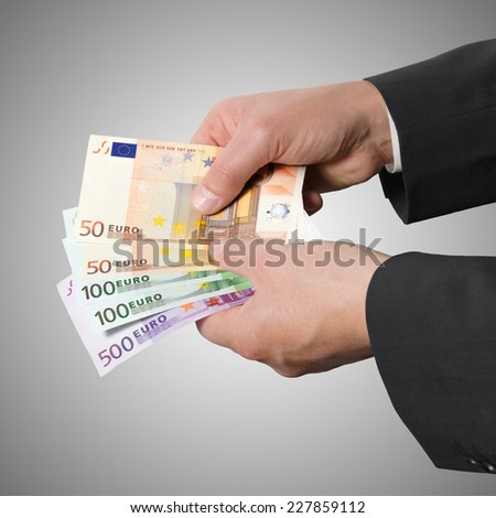 Male hands holding money and counts euro banknotes isolated on a gray background - stock photo