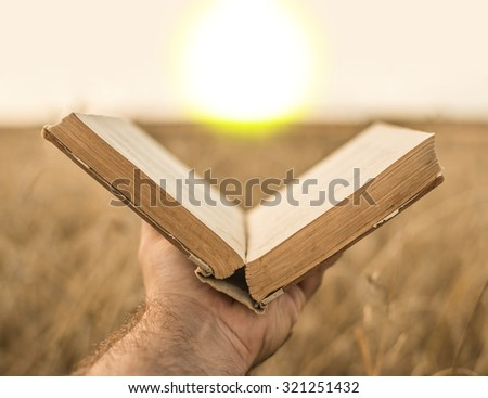 male hands holding opened hardback book, diary with fanned pages on blurred nature landscape background against wheat field and sunset sky back to school education concept. - stock photo