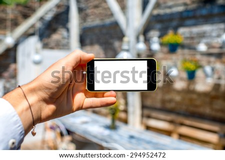 Male hands holding phone with isolated screen on white vintage interior background - stock photo