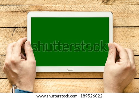 Male hands holding tablet pc with green empty screen on wooden background - stock photo